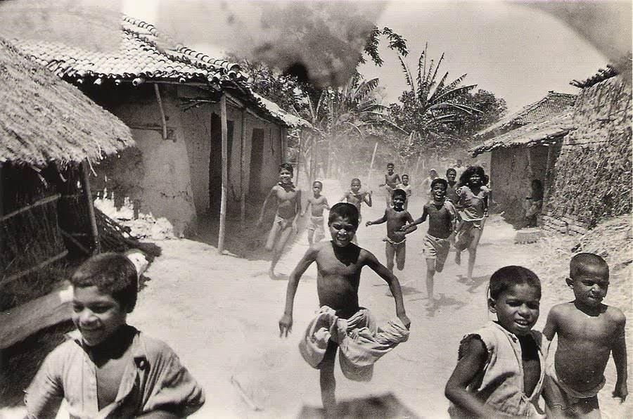 Children running toward trucks delivering famine relief, Bahar, India.